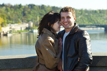 young couple on a bridge on the river