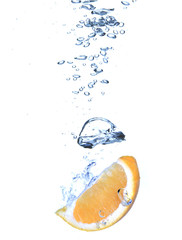 Fresh orange dropped into the water