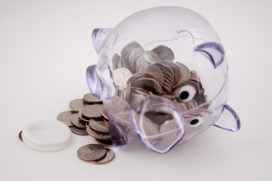 piggy bank on side, with coins spilling out