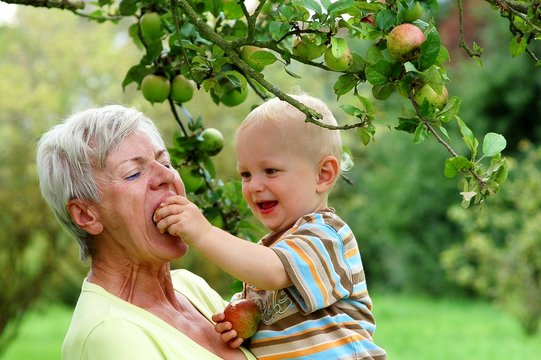 Grandmother with child under apple tree