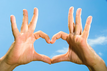 male hands folded in the shape of the heart