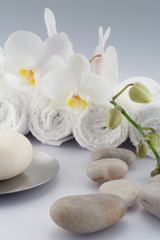 White rolled towels with orchid and soap
