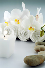 White rolled towels with orchid and candle, stone