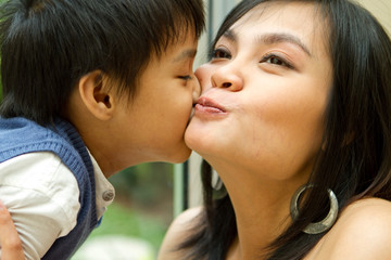 Asian boy and mother kissing