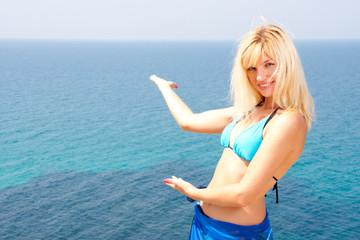 Blonde in bikini inviting to sea