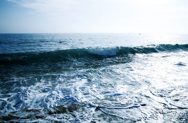 foamy shore blue waves in a clear summer day