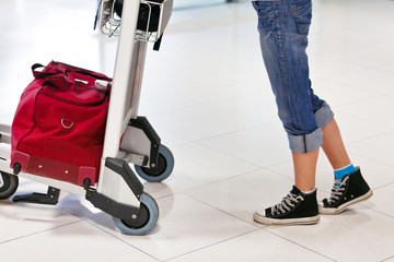 Close up of woman's legs and feet with luggage cart with bag