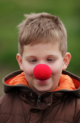 Silly boy smile in red clown nose
