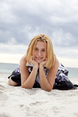 Fotobehang Beautiful blonde girl lying on sand at the beach in rainy day.