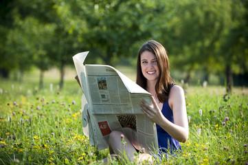 Junge Frau liest eine Zeitung