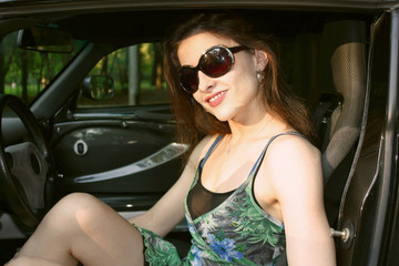 The beautiful girl is sitting in the sport car