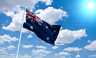 Australian Flag in front of vivid, sunny, cloudy sky