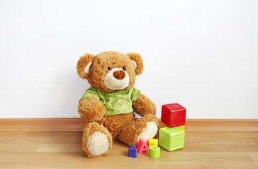 Toys - Teddy bear with cubes on laminate floor