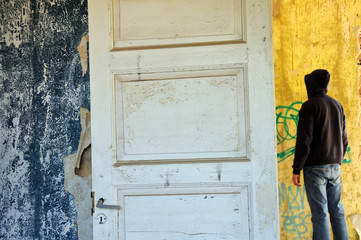 Hooded figure in abandoned house. Torn wallpaper.