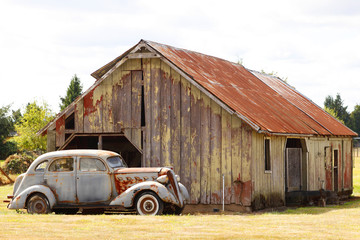 An old car next to a barn.