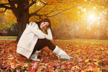 Wall Mural - Portrait of beautiful young woman in autumn park. Copyspace.