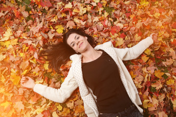 Wall Mural - Portrait of beautiful young woman lying on yellow autumn leaves