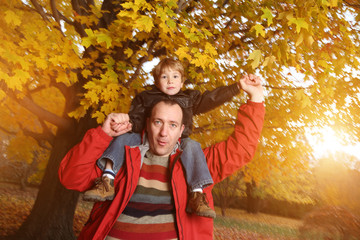 Wall Mural - Father giving son piggyback ride on his shoulders in autumn park