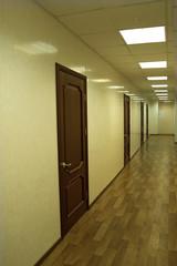 Several brown doors in the corridor office