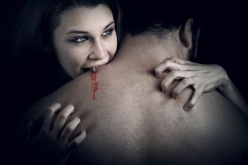 Evil vampire girl sucking blood from lover neck
