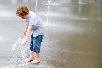Cute little boy playing with water outdoors