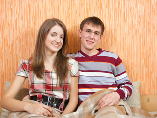 Young happy couple on sofa at home