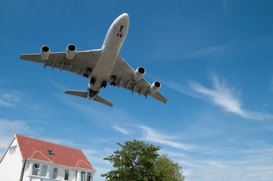 large jet aircraft on landing over suburban housing