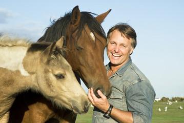 Man petting his horses.