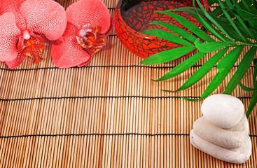 Spa items. Orchid, stones, palm, water on bamboo background