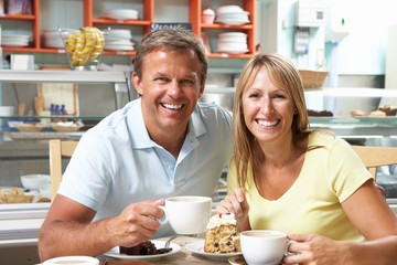 Couple Enjoying Slice Of Cake And Coffee In Cafe