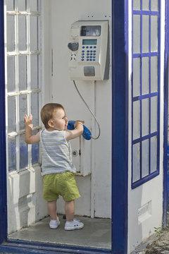 Bebé en una cabina telefónica.