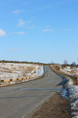 Asphalt country road in early spring against a blue sky