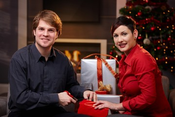 Young couple wrapping christmas gifts