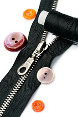 Zipper, thread and button isolated on white