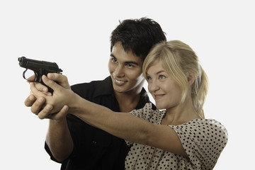 asian man teaches a young woman how to aim a pistol