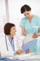 Smiling medical expertise working with assistant