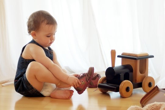 cute child putting shoes on