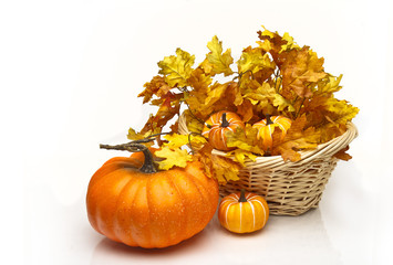 Pumpkins in a wicker basket containing fall leaves.