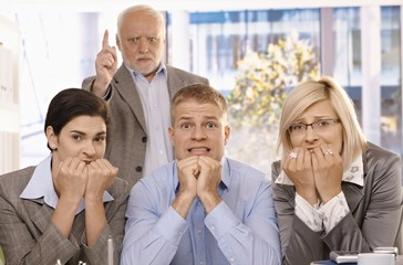 Scared employees sitting with angry boss behind