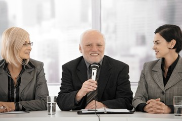 Business meeting, senior man with microphone