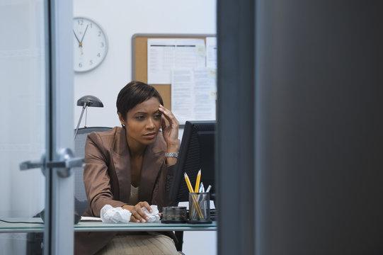 Worried African businesswoman working at computer