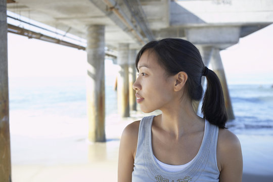 Asian woman under pier at beach