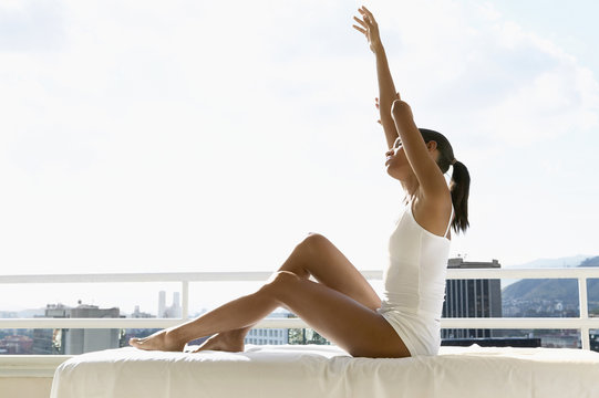 African woman stretching on balcony