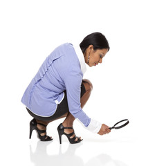 Businesswoman - Latina tracking with magnifying glass