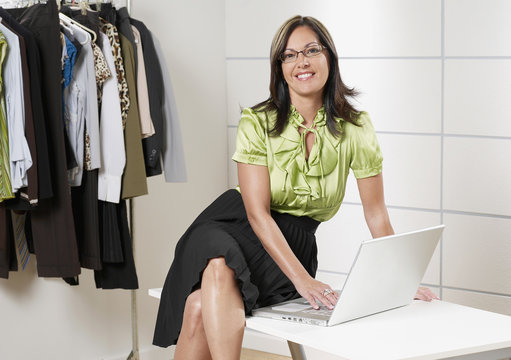 Hispanic businesswoman working on laptop in boutique