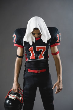 Mixed race football player looking down with towel on head