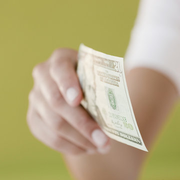 Woman holding twenty dollar bill