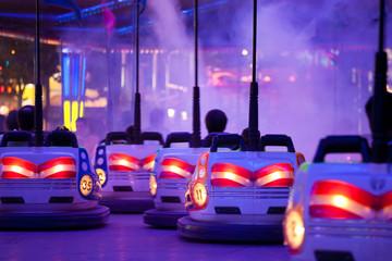 Bumper cars, driving through artificial smoke. Motion blur