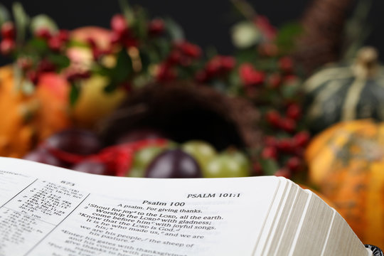 Bible open to Psalm 100 with thanksgiving text and cornucopia