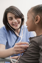 Nurse checking girlÕs heart rate with stethoscope